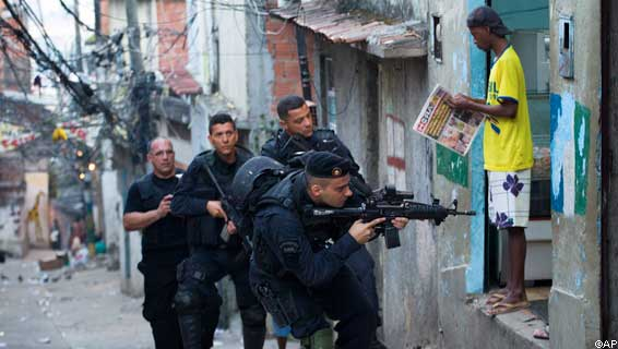 A man reads a newspaperas members of Brazil's special police unit BOPE take positions during a raid of the Mangueira slum in Rio de Janeiro, Brazil